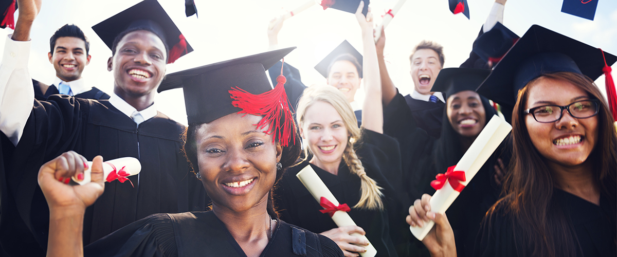 A photo of several teens laughing and smiling in their graduation cap and gown